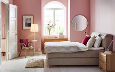 A large bedroom with a beige double bed with an upholstered headboard and bed…