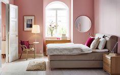 Iso makuuhuone, jossa beige parisänky, jossa pehmustettu ja verhoiltu sängynpääty. Sängyssä beiget ja valkoiset lakanat.