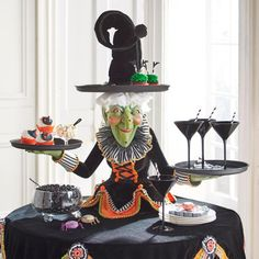 Make the grandest of grand statements, this Halloween, with our spellbindingly sophisticated Witch Tabletop Server at the center of all your frightful    affairs. In short, out of this world! Fascinatingly detailed, from the tip of her plush, posable hat all the way to the separate table topper that serves    as her gown. There are even elaborate gingerbread skeletons suspended from the tips of the topper. As functional to use as it is fun to look at, three    trays  the brim of her hat a...