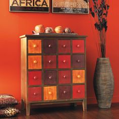 A MULTICOLORED STAINED STORAGE UNIT ADDS COLOR AND STYLE TO AFRICAN INSPIRED SETTING.