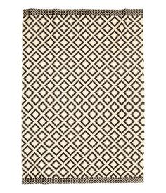 Natural white/charcoal gray. Large cotton rug with a printed pattern.