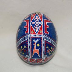 Bold stag, symbolic of wealth, prosperity and leadership. Blue denim background, color symbolic of sky, air, truth and fidelity. This chicken egg measures approx. 2 3/8 x 1 3/4. Egg in pictures is egg I ship you. Ukrainian Decorated Egg – Pysanky. Made in the traditional method of using a kistka to wax on a design, dying the egg a color, then repeating the waxing and dying until desired coverage is attained. The layers of wax are then melted away to reveal a beautiful, decorated eg...