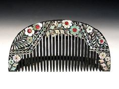 Beautiful Japanese Lacquer Kushi(comb)with Raden finish. Raden is workmenship for Mothers pearl inlaid. This comb has wonderfully detail mothers pearl inlaid. The front has with glass inlaid at flower budd area. The flower is design of Kiku, chrysanthemum. The condition of comb very good except some age wear. A couple of tiny area of line missing. Dating from Taisho period. 1912-1924.