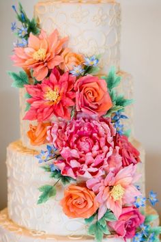 We're obsessed with this chic wedding cake! The bright cascading flowers across all three tiers are to die for!