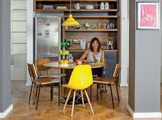 A cadeira amarela vibrante ilumina a cozinha com muita madeira. Projeto do arquiteto Kanô Ferreira para a mãe, Claudia Pinheiro