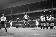 Feyenoord's Johan Cruyff (c) attempts to block Glenn Hoddle's (Tottenham Hotspur) free-kick.