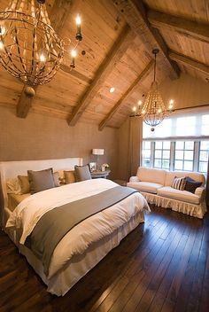 Love the wood-beam ceilings, romantic chandeliers,  coziness of this rustic bedroom... the added couch is a good touch