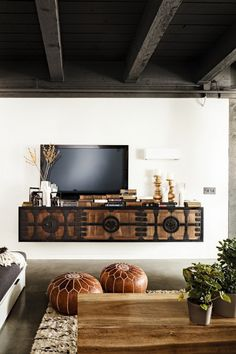Moroccan/boho style living room. Absolutely gorgeous floating timber and wrought iron media unit! Lush rug, timber coffee table and leather poufs.