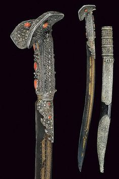 A silver mounted yatagan. Curved, single-edged blade with remains of blueing, decorated with floral & geometrical motifs on the entire length; cylindrical, silver grip with ring-nut, entirely decorated with filigree frames and circles, & several round and drop-shaped coral cabochons; pommel with large ears, decorated with cabochon corals.    dating: early 19th Century;  dimensions: 69 cm.;  Provenance: Turkey