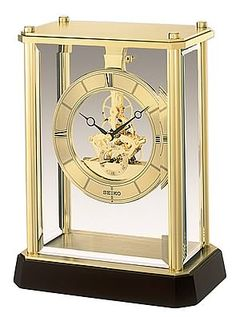 The Seiko Skeleton Mantel Clock has a Gold-tone metal and glass case with a dark brown solid wood base. Heavy, beveled glass with brass frame. Size: H 9 W 7 D Big Clocks, World Clock, Mantel Clocks, Beveled Glass, Seiko, Skeleton, Solid Wood, Quartz, Brass