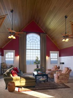 Great room with a huge arch shaped window providing a great view. Slanted tall wooden ceiling, two large hanging fan/lights an antique oriental rug and comfortable furniture make this a very cozy looking room.