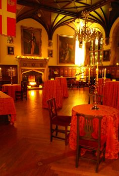 Museum of St John London - Fake fire, battery candle clusters with holly and ivy, wall uplighters in amber, spiral floor standing candelabra with battery candles, coloured table linen, brass table candelabra with battery-powered candles and frosted votive holders by www.stressfreehire.com #venuetransformers