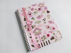 Caderno universitário 10 matérias decorado, forrado com tecido laminado, com guarda em papel color plus, acabamentos com fita de cetim e enfeites. <br> <br>Pode ser feito também como agenda. Pode-se colocar o nome personalizado.