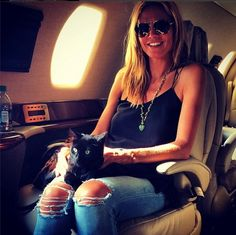 """Known dog lover Heidi Klum shares her seat on a private jet with a new feline friend! """"Kitty,"""" she posted to her Instagram account on Aug. 3, 2014, while she flew home from a trip to Texas."""