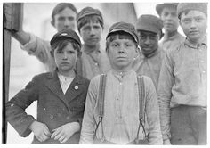 Doffers in Willingham Cotton Mill, Macon, Ga. The three boys in front row have been in mill work for 4, 5 and 6 years respectively. Location: Macon, Georgia. Photographer: Lewis Hine. 1909 January.
