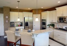 The kitchen in the Bainbridge model features a large island with breakfast bar and a corner walk-in pantry.