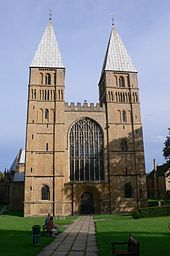 The west front of Southwell Cathedral. A simple Norman west front with two towers surmounted by short pyramidal spires. A large Gothic window has been inserted between the towers.