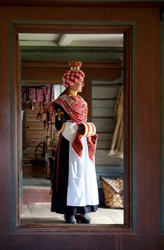 She is dressed and ready to leave for church. The floral headdress is made of leather and decorated with paper flowers. There is an opening at the top, so that her pleated hair can come out. The hair...