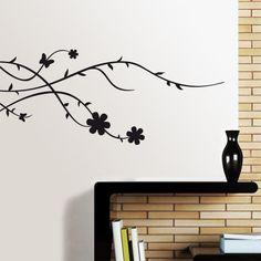 Minimalista diseño floral. Vinilo decorativo formado por ramas de líneas sinuosas entrelazadas, unas flores y una mariposa. La versátil composición del Brunia permite su aplicación tanto en vertical como en horizontal.