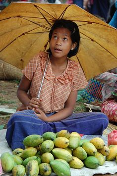 A girl selling mangos in a market, Inle Lake, Myanmar.