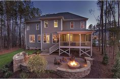 White pillars frame a porch leading to an inviting patio with built-in grill and fire-pit. New homes in the Wrenhurst community from Baker Residential in Cary, NC.