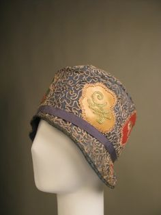 c1925-1930 cloche,Mid blue rayon twill cloche hat with narrow partial brim; the whole entirely covered in vermicular beige silk chainstitch embroidery around irregular patches of pink, yellow and green kid leather, also embroidered in coloured silk chainstitch  Manchester Art Gallery