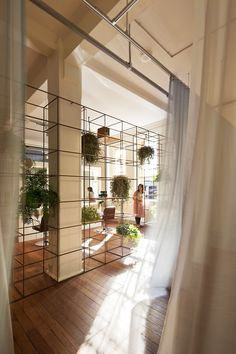 Great way to divide a room while keeping it open and airy - plus the plants!