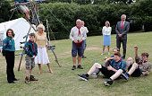 Camilla Duchess of Cornwall watches as Scouts fire a giant catapult they made she visits the Poppy Pod Village at the Tile Barn Outdoor Centre on...