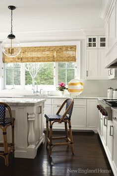 source: New England Home  Jan Hiltz - Beautiful kitchen with floor to ceiling white kitchen cabinets, white kitchen island with turned legs, marble countertops, subway tiles backsplash, Horchow Mini Lightbulb Pendant, French cafe counter stools and bamboo roman shades.