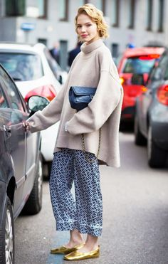 Sasha Luss in a turtleneck, pajama style pants, and gold flats