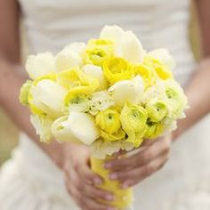 Bridal bouquet made of yellow ranunculas, buttery lisianthus and cream colored tulips.