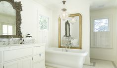 Traditional bathroom with white built-in vanity topped with a white marble counter and backsplash ledge which frames an undermount sink with hook spout faucet below an antiqued carved wood mirror.