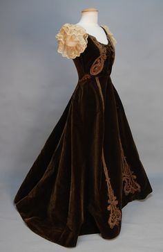 "JACQUES DOUCET VELVET EVENING GOWN with CORDED TRIM c. 1895. 1-piece brown silk with boned low neck sleeveless bodice decorated with colorful braided cord, embroidered net ruffles at shoulder, lined in green silk faille, petersham marked ""Doucet 21, Rue de la Paix"""