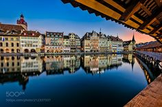 The historical Chapelbridge with the btfl Old Town - The historical wooden Chapelbridge in Lucerne with the old town mirrored in the river Ruess. A perfect Sunrise!