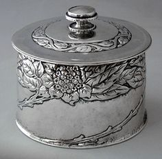 OMAR RAMSDEN (1873-1939) & ALWYN CARR (1872-1940) A lightly hammered, cylindrical silver box, decorated with flowering branches. The lid with a final set mother-of-pearl. Size: Diameter of lid 10.4 cm. base 10.4 cm. Height approximately 9 cm. Mark for Ramsden & Carr. Hallmarks for London 1907. SOLD