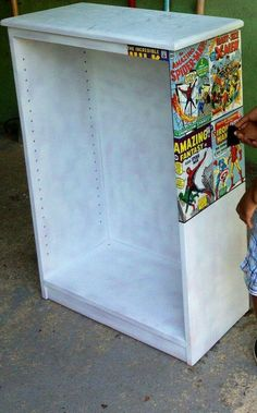 Glue old superhero magazine covers to a bookshelf...love it for a little boys room!!