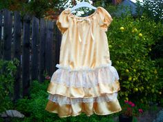Party dress in sparkly gold satin with tierd ruffles in satin and cream lace.  Dress is finished with a gold and cream bow in the front.  Dress features elastic collar and puff sleeves.  2T, 3T, 4T, 5 years, 6 years or 6X  $55