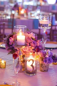 Gorgeous purple centerpiece with candles and flowers.