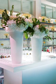 Fresh hydrangeas and monstera leaves make for beautiful floral arrangements that punctuate the all-white decor.