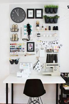 Mesa de escritorio de superficie blanca y patas negras, silla negra. Sobre la mesa dos máquinas de coser. Muro con panel de madera perforado blanco con organizadores para los hilos, las tijeras, un reloj, un par de maceteros con plantas y fotografías e ilustracioneas enmarcadas.