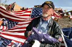 Fred Myers holds a flag to discard onto the pile at the 2015 Watchfire.