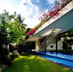 Located in Singapore, the Tannga House is a tropical paradise with the home being built around a green courtyard to enjoy the hot climate. Designed by Guz Architects, the L-shaped house is all about the outdoors and the lush landscape that surrounds it. But that's not all – the house also features an L-shaped, glass-walled pool that can be viewed through a window from a lower floor in the home.