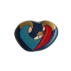 """ROCK A+heart-shaped,+smooth+stone+features+the+Holy+Family+hand+painted+on+one+side+in+teal,+red+and+metallic+gold+against+a+midnight+blue+background.+The+reverse+side+is+painted+with+gold+metallic+paint+and+""""He+is+my+Rock""""+is+hand+lettered+in+black. Pebble Painting, Stone Painting, Rock Painting, Christmas Rock, Christmas Signs, Christmas Ideas, Christmas Crafts, Christmas Decorations, Family Painting"""