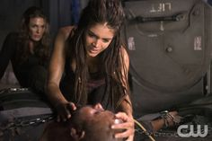 """The 100 -- """"Long Into an Abyss"""" -- Image: HU207a_0204 -- Pictured (L-R): Paige Turco as Abby, Marie Avgeropoulos as Octavia, and Ricky Whittle as Lincoln-- Photo: Cate Cameron/The CW -- © 2014 The CW Network, LLC. All Rights Reservedpn"""