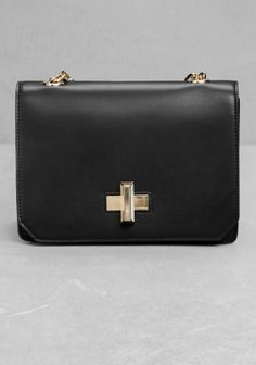 Half leather and half chain strap carries this sleek leather bag embellished with a lustrous mother-of-pearl twist-lock closure.