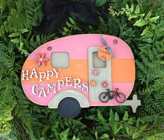 """""""Happy Campers"""" Hanger  Includes: Pink and Orange Camper Hanger, """"Happy Campers"""", as well as the Medium Daisy, Small Daisy, Bicycle, and Personalized Tag accent shapes as shown. Measurements: 7"""" x 10.5"""" Price $33.95 See website for full pricing and customizing details."""