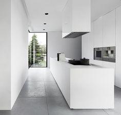 cocina minimalista blanca abierta al jardín, con módulo empotrado e isla central con zona de cocción y fregadero, suelo baldosas color gris