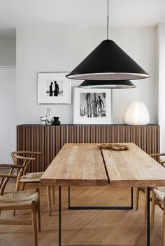 Great wood table and sideboard with black pendant lights in the dining room.