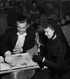 Clark Gable and Vivien Leigh, playing a game of Chinese Checkers on the set of Gone With the Wind (1939).