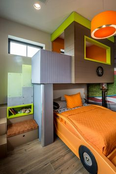 "To create a one of a kind bunkbed in this racetrack inspired room, designer Carrie Maniaci built the upper bunk as the garage with the lower bunk as the car parked underneath. ""We wanted something that would be fun for the kids and spark their imagination,"" Maniaci said."